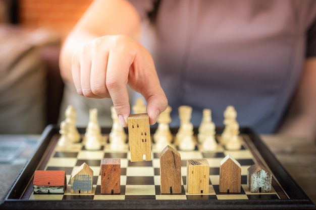 Hand of business woman moving chess to building and house models in chess game Premium Photo