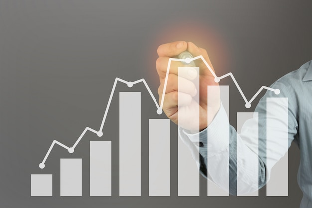 Hand of a businessman holding a pen point to top bar graph. Premium Photo