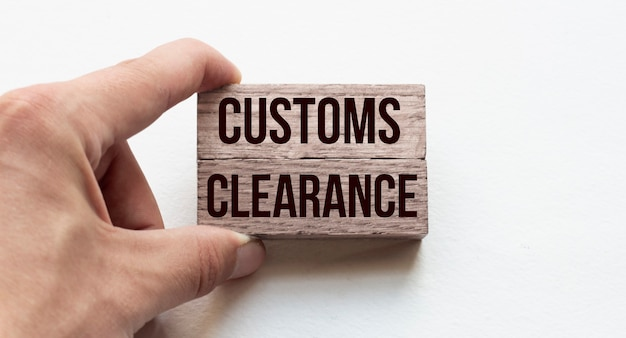 Hand of a businessman holding wooden blocks conceptual image text customs clearance