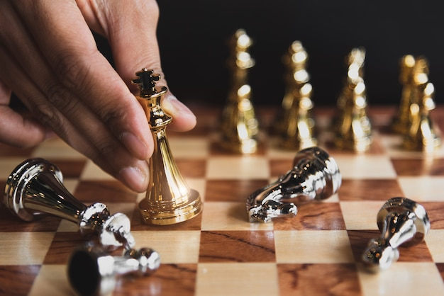 Hand of businessman moving chess for eliminating in battle competition with successful end Premium Photo