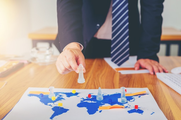 Hand of businessman playing chess with world map as a board. business strategy concept. Premium Photo