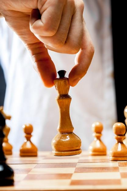 Hand of businessman playing chess Premium Photo