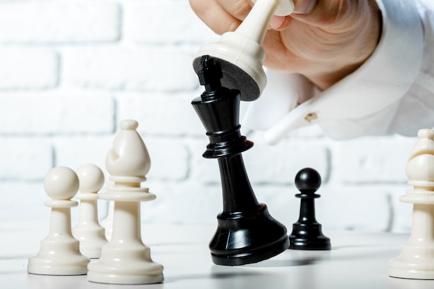Hand of businessman playing chess Premium Photo