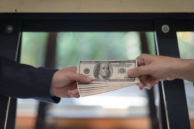 Hand businessman sealing the deal with a handshake and receiving a bribe money. Premium Photo