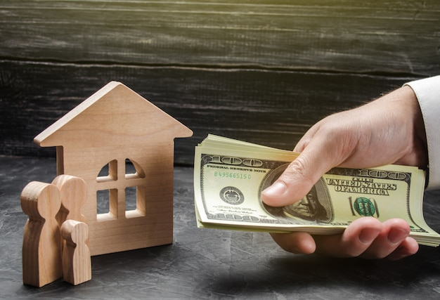 The hand of a businessman stretches a wad of money to the family figures near the wooden house Premium Photo