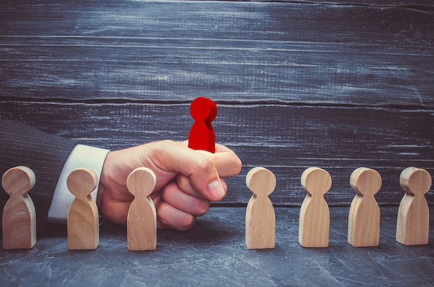 Hand of a businessman takes a red wooden figure of a man. the concept of search Premium Photo