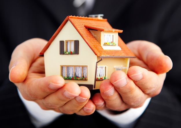 Hand of the businessman with the house. Premium Photo