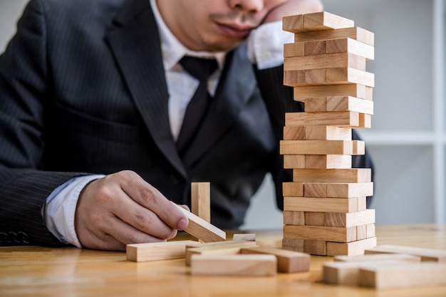 Hand of businesspeople placing and pulling wood block on the tower, alternative risk concept Premium Photo