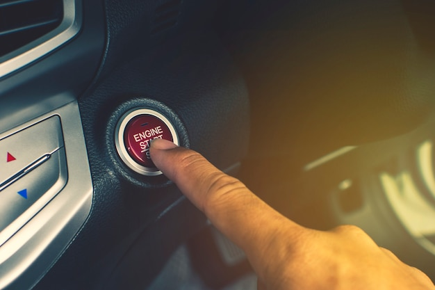 Hand of car driver press to the engine start/stop button for engine ignition in a luxury car. Premium Photo