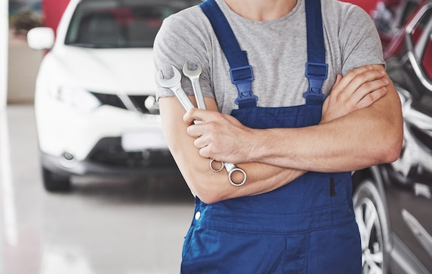 Hand of car mechanic with wrench. auto repair garage. Free Photo