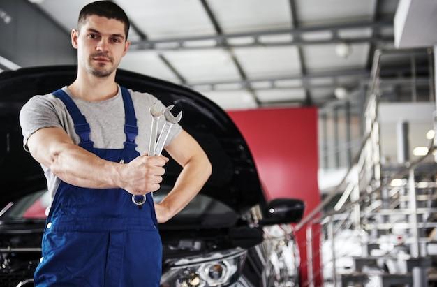 Mano del meccanico di automobili con la chiave. garage per riparazioni auto. Foto Gratuite