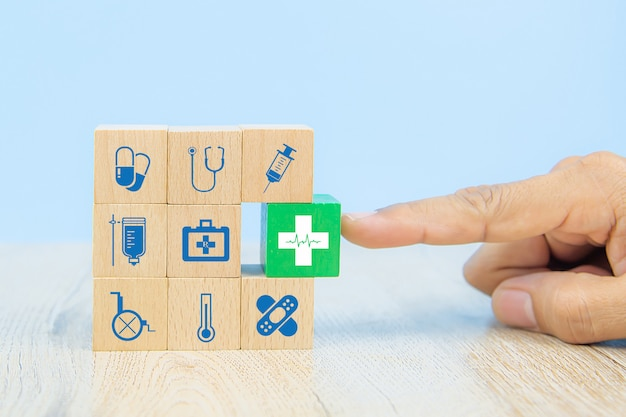 Hand choose medical icon on cube wooden toy blocks stack in with other medical symbols. Premium Phot