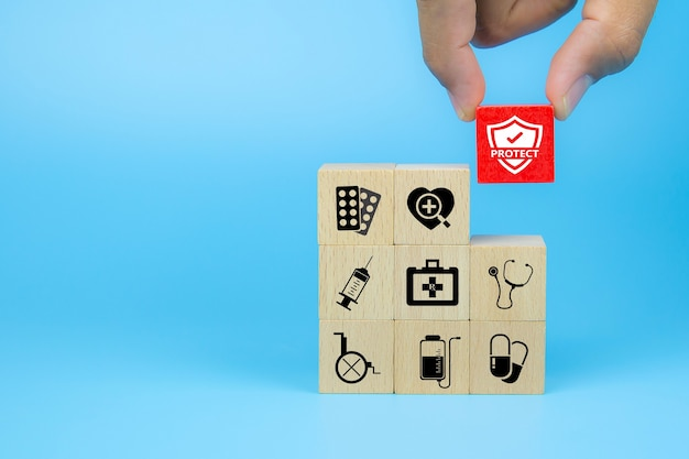 Hand choose medical icon on cube wooden toy blocks stack in with other medical symbols Premium Photo