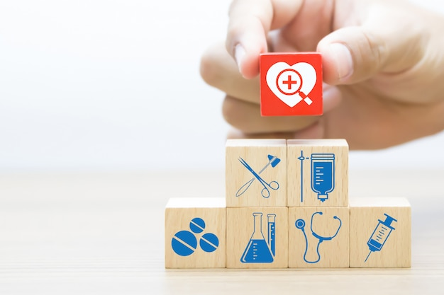 Hand choose wooden block with medical and health icon. Premium Photo