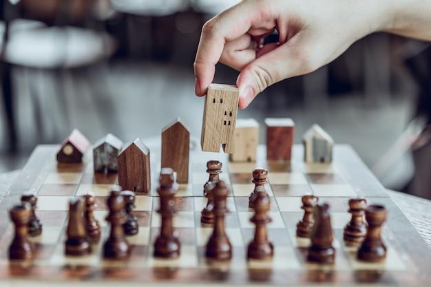 Hand choosing mini wood house model from chess game, choose