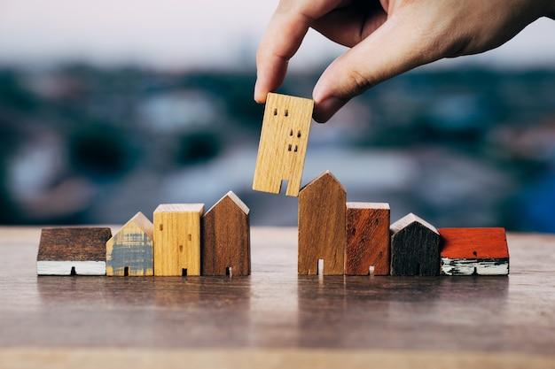 木のテーブルの上のコインのお金のモデルと行からミニ木造住宅モデルを選択する手 Premium写真