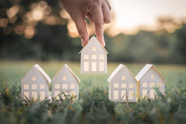 Hand choosing white paper house model from group of house on green grass. Premium Photo
