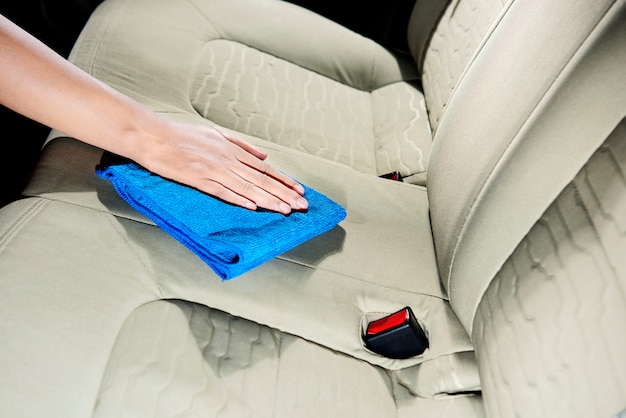 Hand cleaning car interior with rag cloth Premium Photo