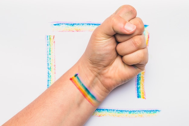 Hand clenched into fist with stripes in lgbt colors Free Photo