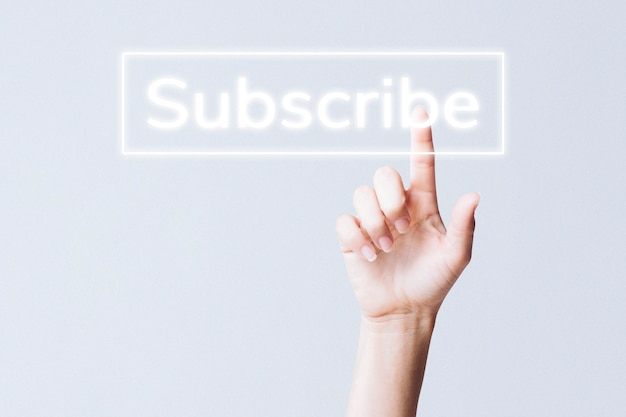 Hand clicking subscribe button on social media Free Photo