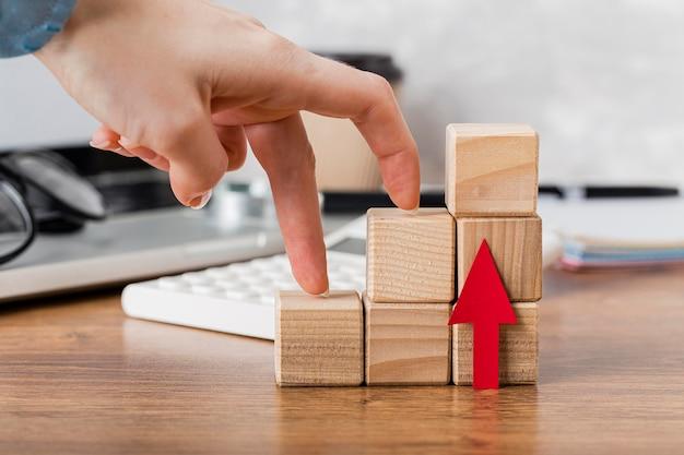 Arrampicata a mano su blocchi di legno per rappresentare la crescita Foto Gratuite