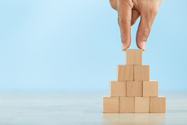 Hand closer up hands of businessmen,stacking wooden blocks into steps,concept of business growth success Premium Photo