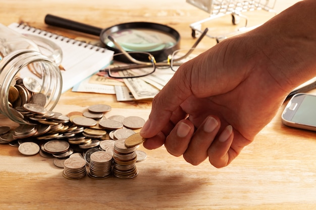 Hand coins in fingers and row stacks of coins with business objects on wood Premium Photo