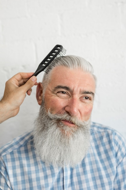 Hand combing old man gray hair Free Photo