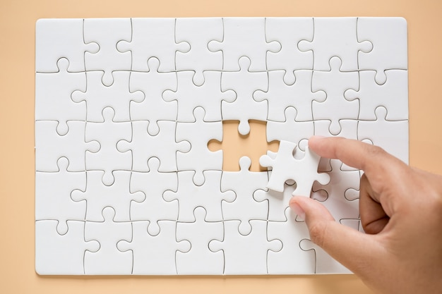 Hand connecting puzzle pieces on table background Free Photo
