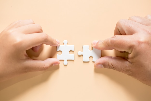 Hand connecting puzzle pieces on table Free Photo