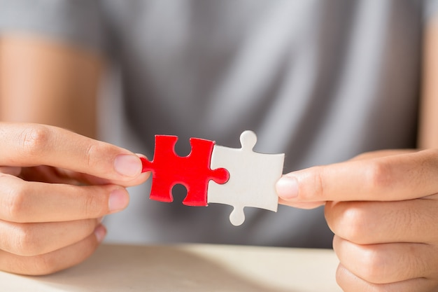 Hand connecting two puzzle pieces on table background Free Photo