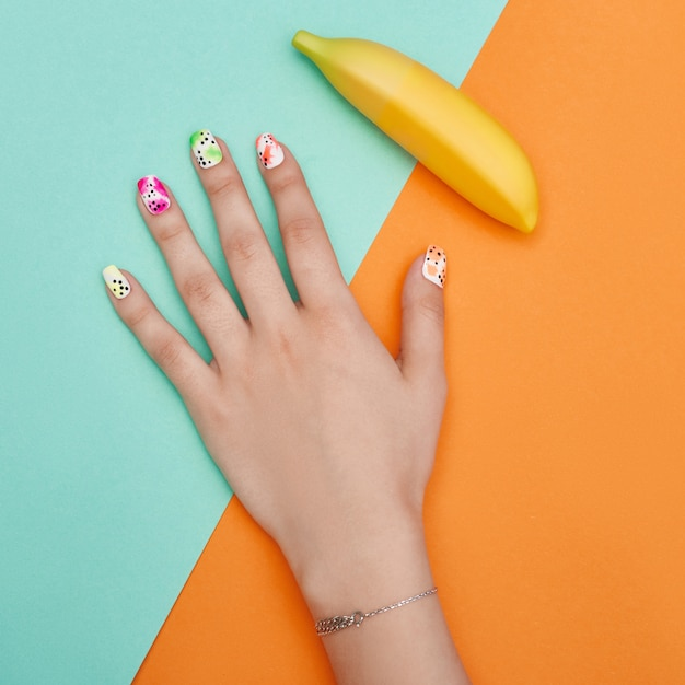 手の化粧品の爪の色とケア、プロのマニキュアとケア製品。色紙の背景の上に横たわる手 Premium写真