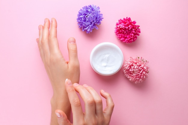 Hand cream and flowers. skin and hand care. moisturizing and eliminating the dryness of the hands skin Premium Photo