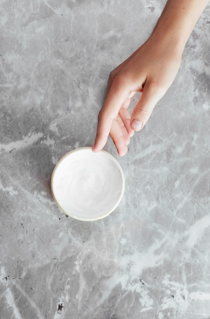 Hand and cream on marble background Free Photo