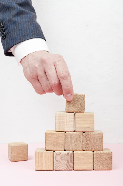 Hand creating pyramid from wooden cubes Free Photo
