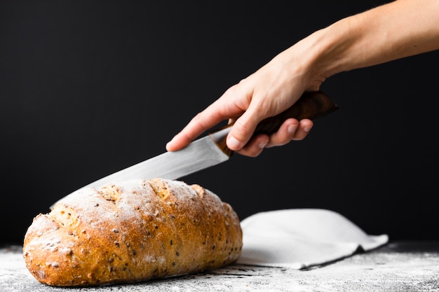 Hand cutting bread loaf with knife Free Photo