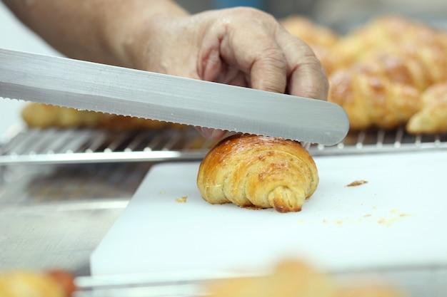 Hand cutting croissant Premium Photo