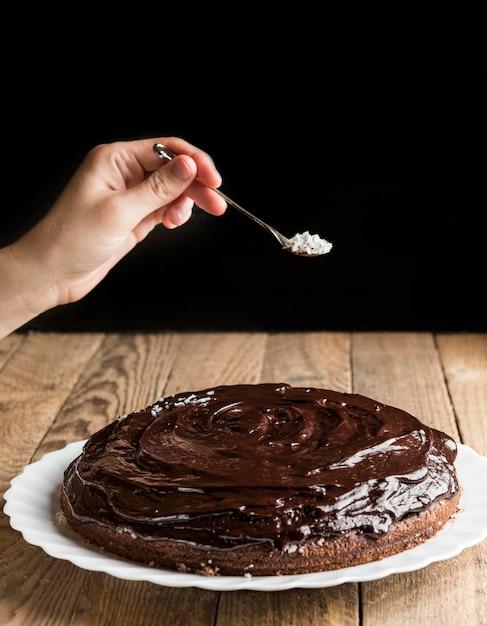 ココナッツフレークでチョコレートケーキを飾る手 無料写真