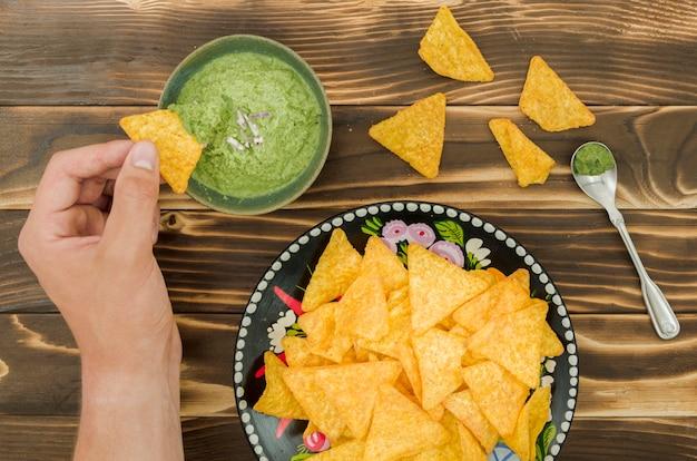 Hand dipping nachos in guacamole Free Photo
