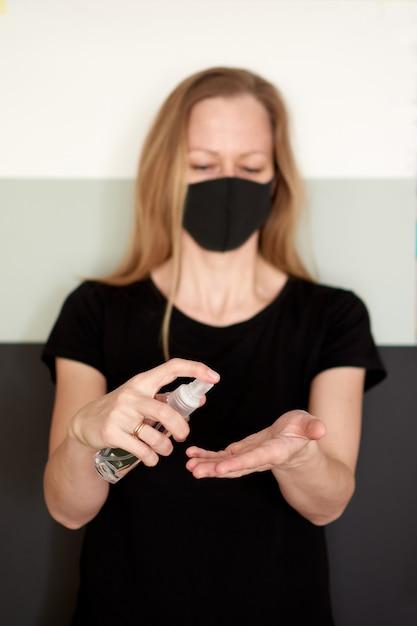 検疫中にスプレー消毒剤でコロナウイルスを保護するための手指消毒。 Premium写真