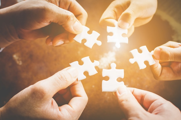 Hand of diverse people connecting jigsaw puzzle. concept of partnership and teamwork in business Pre