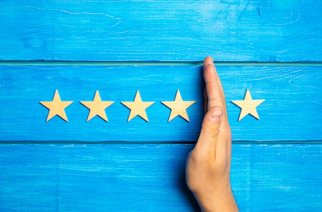 The hand divides the fifth star from the four others. rating 5 stars, 4 stars. overview Premium Photo