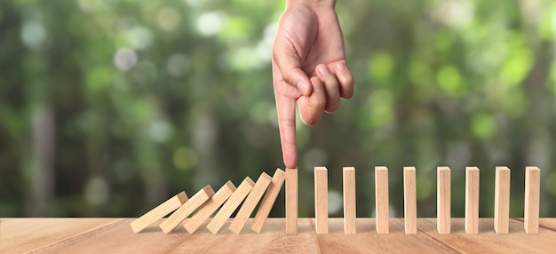 Hand and domino effect stopped by unique Premium Photo
