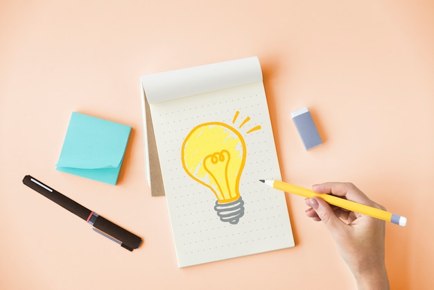 Hand drawing a light bulb on a notepad Premium Photo