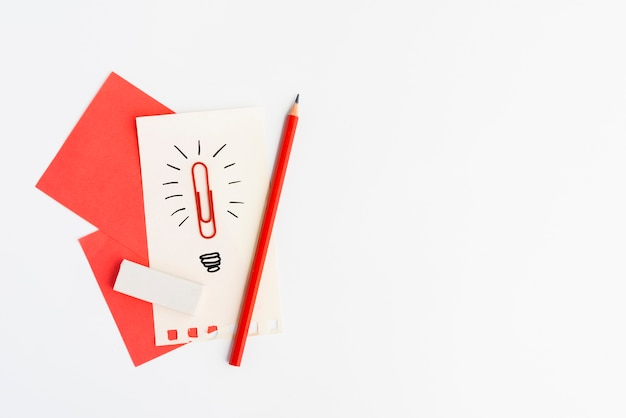 Hand drawn creative idea sign made from paperclip on paper over white background Free Photo