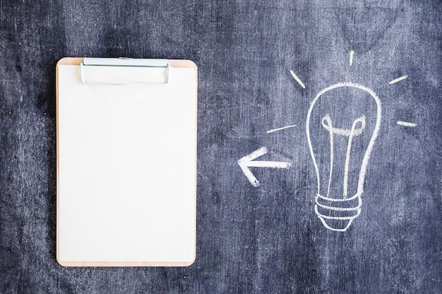 Hand drawn light bulb and clipboard on blackboard Free Photo