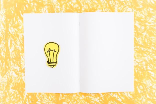Ручная лампочка на белом фоне над желтым текстурированным фоном Бесплатные Фотографии