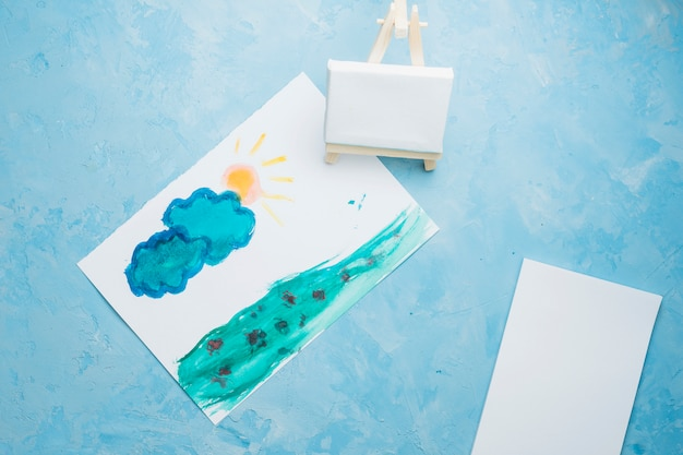 Hand drawn paper painting with mini easel on watercolor backdrop Free Photo