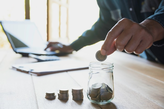 Hand drop a coin with money coin stack growing for business Premium Photo