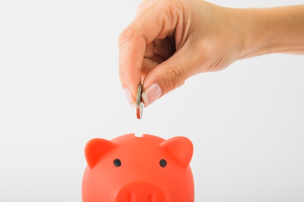 Hand dropping coin in piggy bank Premium Photo